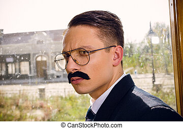 old photo of serious man in suit with a mustache and glasses on