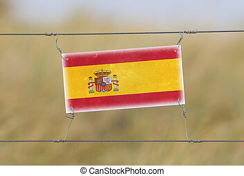 Border fence - Old plastic sign with a flag - Spain