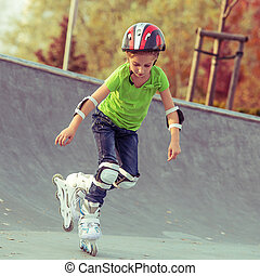 Little girl on roller skates in helmet at a park