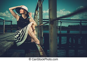 Beautiful woman wearing hat and white scarf sitting on old...