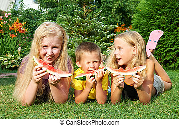 Happy children eating watermelon in the garden