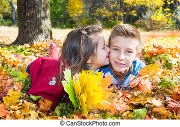 Fall. Brother and sister with leaves in autumn park
