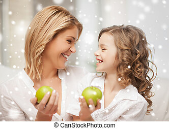 happy mother and daughter holding green apples - family,...