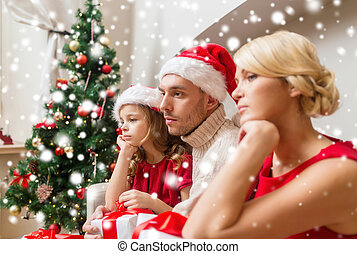 sad family with gift boxes at home - christmas, holidays,...