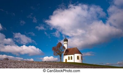 timelapse of moving clouds at blue sky over single chapel in...