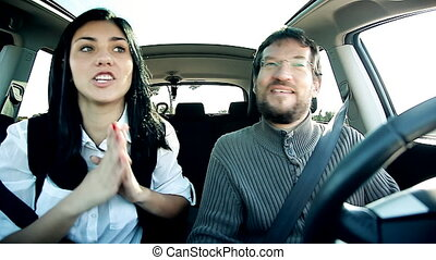 Couple making funny faces in car - Couple in car making...