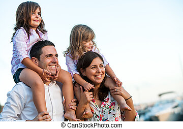 Young couple with kids on shoulders outdoors.