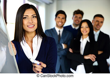 Smiling business team with flip board in office