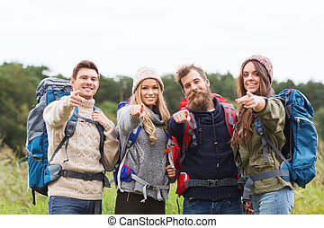 smiling hikers with backpacks pointing finger - adventure,...