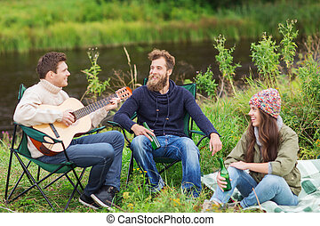 group of tourists playing guitar in camping - adventure,...