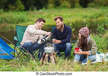 group of smiling tourists cooking food in camping -...