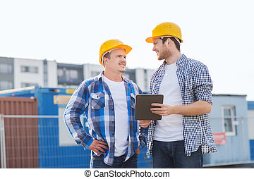 smiling builders in hardhats with tablet pc - business,...