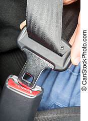 Person fastening a seatbelt in a car - Close up of the hand...