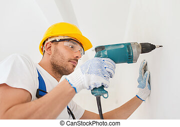 builder in hardhat working with drill indoors - building,...