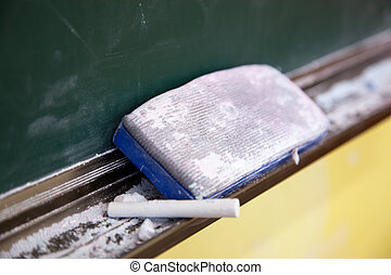 Chalk and brush resting on black board in a classroom