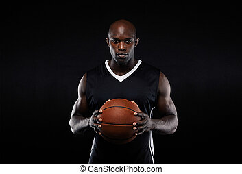 Muscular young male basketball player in uniform