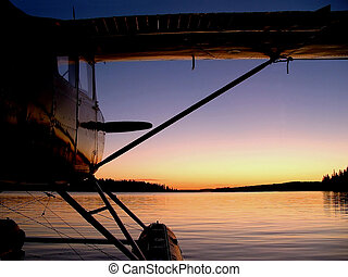 Dawn Departure - A float plane waits for takeoff on a calm...