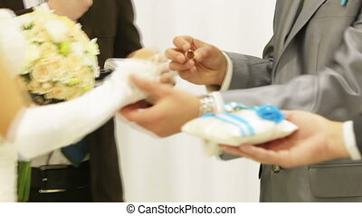 Donning ring - Bride putting wedding ring groom