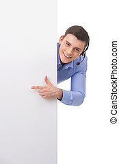 Smiling customer service male operator pointing to blank white billboard. male hiding behind white board and smiling