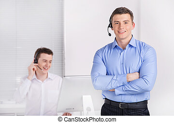two young call center men talking by phone Two male...