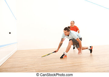 Two men playing match of squash Squash players in action on...