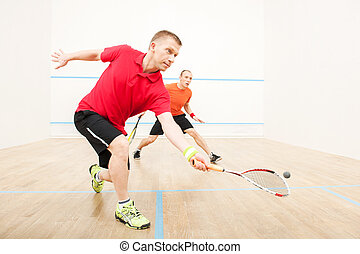 Two men playing match of squash Closeup of squash players in...