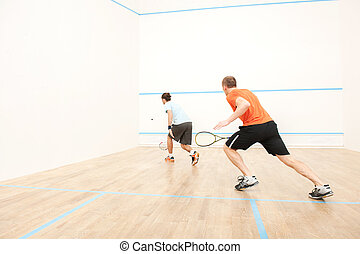 Two men playing match of squash Back view of squash player...