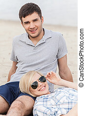 Attractive young couple sitting on beach at summer. happy woman lying on man's legs in glasses