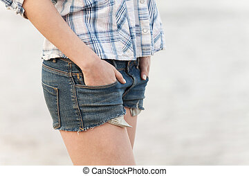 woman in jeans shorts walking on sand closeup on girl...