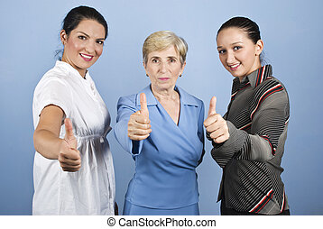 Successful business women giving thumbs up - Three business...