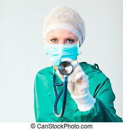 Surgeon holding stethescope outwards - Young female Surgeon...
