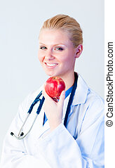 Doctor holding an apple with focus on person - Young female...