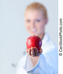Doctor holding an apple with focus on the apple