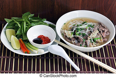 Beef Noodle Pho - Pho Beef noodle soup eating with basil