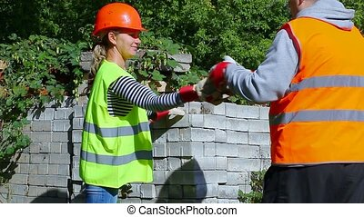 Builders with bricks in the hands