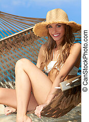 Gorgeous blond woman relaxing in a hammock