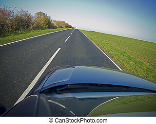 A car drives down a long straight road on a colorful day....