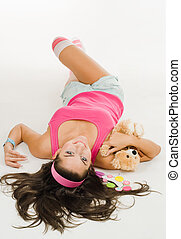 Woman with toy lay on the floor in vivid bright clothes with...