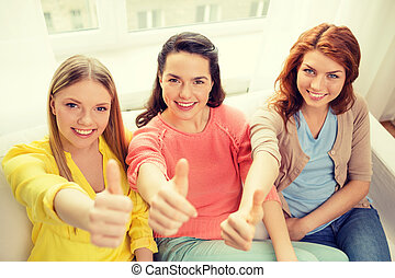 three girlfriends showing thumbs up at home - friendship,...