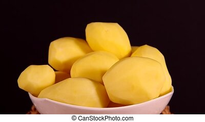 Peeled potatoes are rotating on a black background.