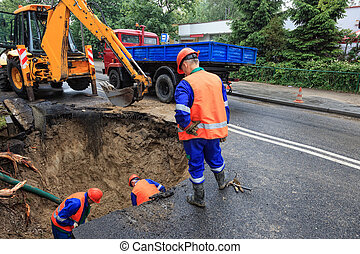 Damaged road - Workers repairing the damaged road - rupture...