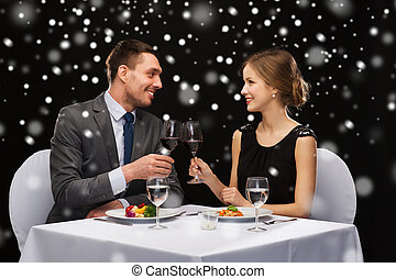 smiling couple at restaurant - food, christmas, holidays and...