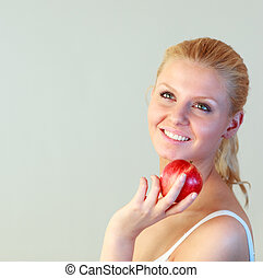 Friendly woman holding an apple with focus on woman
