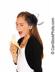 Girl eating banana - A lovely young girl standing in a...