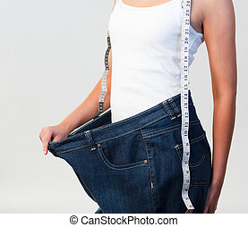 Close-up of woman wearing big jeans focus on woman -...