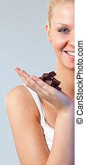 Close-up of an attractive woman holding chocolate focus on woman