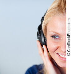 Close-up of a friendly woman listening music with headphones
