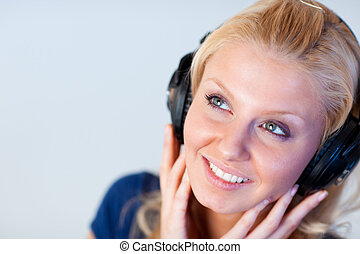 Close-up of an attractive woman with headphones in front of...