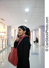 Indian Woman talking on phone in a mall