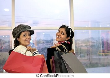 Group of happy smiling women shopping with colored bags.